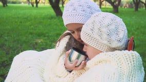 Deux filles boivent du thé en parc Soyez passionné Plan rapproché banque de vidéos
