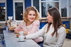 Deux filles buvant du café dans un café Photographie stock