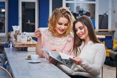 Deux filles buvant du café dans un café Photographie stock libre de droits