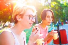 Deux filles buvant du café en parc Photos stock