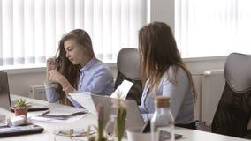 Deux filles cheking leurs documents au bureau L'un d'entre eux ont trouvé une erreur énorme banque de vidéos