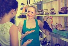 Deux filles choisissant des chaussures dans le magasin Photographie stock libre de droits