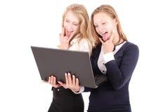 Deux filles choquées à l'aide de l'ordinateur portable Photo stock