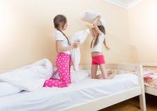 Deux filles combattant avec des oreillers à la chambre à coucher Photographie stock