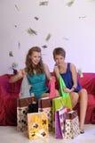 Deux filles considèrent et se montrent des achats Photos stock