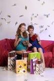 Deux filles considèrent et se montrent des achats Photo stock