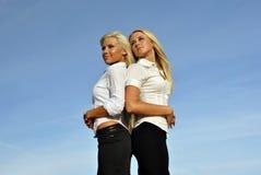 Deux filles contre le ciel. l'espace pour le texte Photographie stock libre de droits