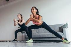 Deux filles convenables faisant la séance d'entraînement à la maison exécutant des mouvements brusques latéraux à la maison photo libre de droits