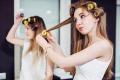Deux filles courbant leurs cheveux avec des rouleaux dans une chambre Images stock