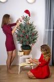 Deux filles décorent un arbre de Noël Photographie stock