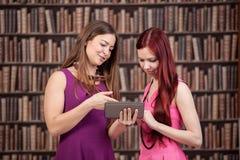 Deux filles d'étudiant apprenant dans la bibliothèque Photos stock