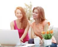 Deux filles d'étudiant regardant l'ordinateur portable examinent tout en se reposant sur Photos stock