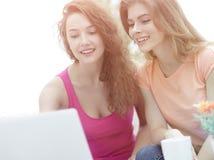 Deux filles d'étudiant regardant l'ordinateur portable examinent tout en se reposant sur Photo libre de droits