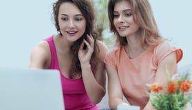 Deux filles d'étudiant regardant l'ordinateur portable examinent tout en se reposant sur Images stock
