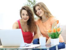 Deux filles d'étudiant regardant l'ordinateur portable examinent tout en se reposant sur le divan Photo libre de droits