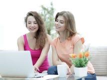 Deux filles d'étudiant regardant l'ordinateur portable examinent tout en se reposant sur le divan Photo stock