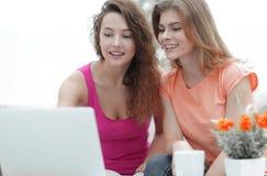 Deux filles d'étudiant regardant l'ordinateur portable examinent tout en se reposant sur le divan Photos stock