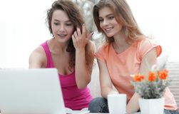 Deux filles d'étudiant regardant l'ordinateur portable examinent tout en se reposant sur le divan Photographie stock libre de droits