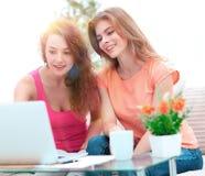 Deux filles d'étudiant regardant l'ordinateur portable examinent tout en se reposant sur le divan Image stock