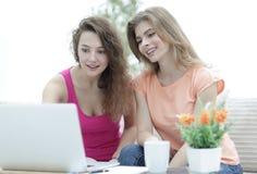 Deux filles d'étudiant regardant l'ordinateur portable examinent tout en se reposant sur le divan Photographie stock