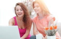 Deux filles d'étudiant regardant l'ordinateur portable examinent tout en se reposant sur le divan Image libre de droits