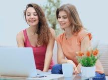 Deux filles d'étudiant regardant l'ordinateur portable examinent tout en se reposant sur le divan Images stock