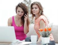 Deux filles d'étudiant regardant l'ordinateur portable examinent tout en se reposant sur le divan Images libres de droits