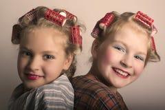 Deux filles d'adolescent jouant des femmes au foyer, se font des coiffures et maquillage ayant l'amusement Image libre de droits