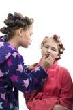 Deux filles d'adolescent jouant des femmes au foyer, se font des coiffures et maquillage ayant l'amusement Image stock