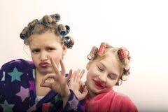 Deux filles d'adolescent jouant des femmes au foyer, se font des coiffures et maquillage ayant l'amusement Photo stock