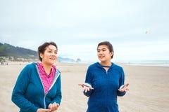 Deux filles d'adolescent marchant sur la plage le jour nuageux frais Photographie stock libre de droits