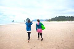 Deux filles d'adolescent marchant sur la plage le jour nuageux frais Image libre de droits