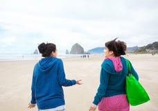 Deux filles d'adolescent marchant sur la plage le jour nuageux frais Photographie stock