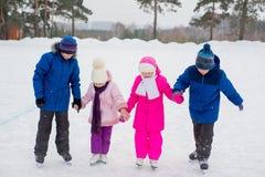 Deux filles d'aides de garçons apprennent à patiner Images stock
