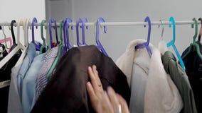 Deux filles d'amis choisissent des vêtements dans la garde-robe, cintres mobiles et frottent le tissu à la main, vue de détail banque de vidéos