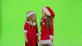 Deux filles d'enfants jurent et discutent, elles sont dans des costumes colorés Écran vert banque de vidéos