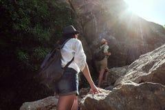 Deux filles d'une amie de touristes du ` s escaladent les montagnes, s'aident, atteignent un coup de main Photographie stock libre de droits