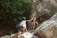 Deux filles d'une amie de touristes du ` s escaladent les montagnes, s'aident, atteignent un coup de main Images libres de droits