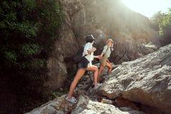 Deux filles d'une amie de touristes du ` s escaladent les montagnes, s'aident, atteignent un coup de main Photos libres de droits