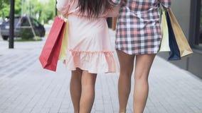 Deux filles dans de belles robes vont après l'achat près du centre commercial tenant des paquets avec des achats ayant un bon banque de vidéos