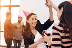 Deux filles dans des chapeaux de fête parlent dans le bureau Photos libres de droits