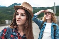Deux filles dans des chapeaux voyageant et faisant de l'auto-stop Photographie stock libre de droits