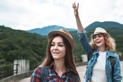 Deux filles dans des chapeaux voyageant et faisant de l'auto-stop Photo libre de droits
