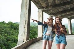 Deux filles dans des chapeaux voyageant par des ruines Images stock