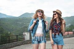 Deux filles dans des chapeaux voyageant par l'ander de ruines pleuvoir Photos stock