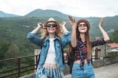 Deux filles dans des chapeaux voyageant par l'ander de ruines pleuvoir Photographie stock