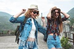 Deux filles dans des chapeaux voyageant par l'ander de ruines pleuvoir Image stock