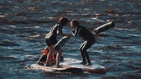 Deux filles dans des gilets de vie combattant avec les panneaux surfants de battes molles dans l'eau banque de vidéos