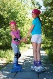Deux filles dans des patins de rouleau regardant l'appareil-photo Images libres de droits