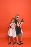 Deux filles dans des robes militaires avec des bras à disposition et des lunettes de soleil o Image libre de droits